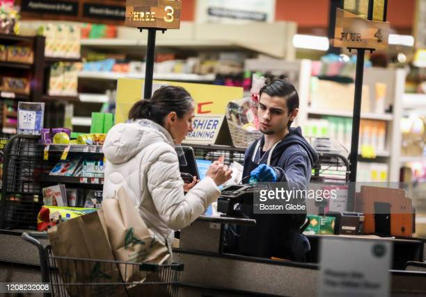 Cashier wears gloves while scanning the groceries of a customer at a Whole Foods in Cambridge, MA on March 24, 2020. Grocery stores have become even...