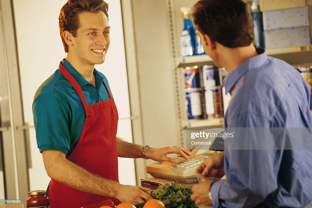 Cashier with customer at grocery store : Stock Photo