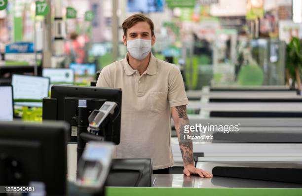 cashier working at a supermarket wearing a facemask - cashier stock pictures, royalty-free photos & images
