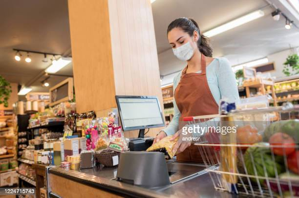 cashier working at the supermarket wearing a facemask while scanning products - cashier stock pictures, royalty-free photos & images