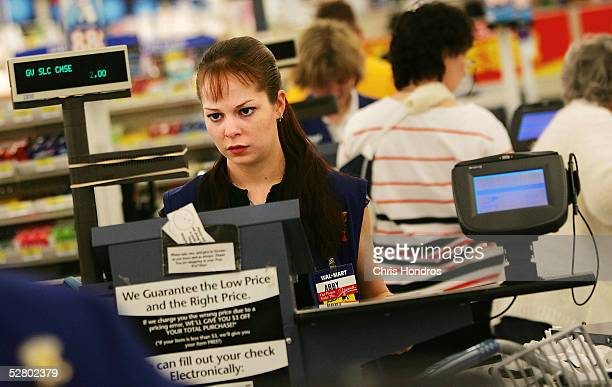 A cashier works at the checkout counter of a WalMart Supercenter May 11 2005 in Troy Ohio WalMart America's largest retailer and the largest company...