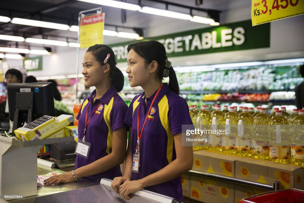 Cashiers stand at a check out counter inside a City Mart Supermarket store, operated by City Mart Holdings Co., in Yangon, Myanmar, on Saturday, March 11, 2017. City Mart has 20 years of market knowledge to help it compete against international players, said Win Win Tint, managing director of City Mart in a Bloomberg interview on March 9. Photographer: Brent Lewin/Bloomberg via Getty Images