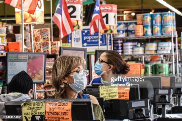 Cashiers wearing protective masks work in a grocery store in the Bushwick neighborhood of Brooklyn on April 2 2020 in New York City New York City is...