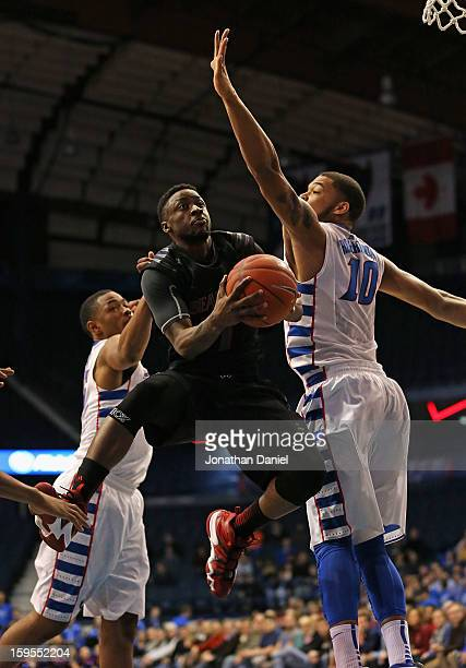 Cashmere Wright of the Cincinnati Bearcats drives between Moses Morgan and Derrell Robertson Jr #10 of the DePaul Blue Demons at Allstate Arena on...