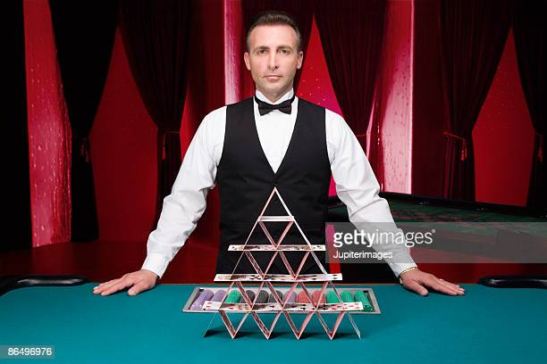 Casino dealer with house of cards