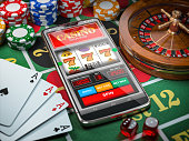 Casino online. Smartphone or mobile phone, slot machine, dice, cards and roulette on a green table in casino.