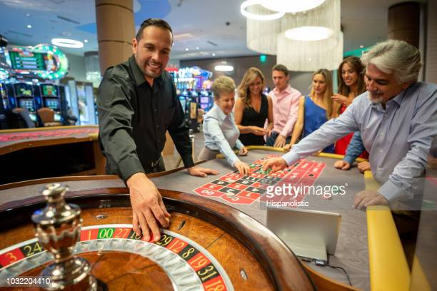 casino worker ready to release the ball on the roulette wheel while others are still placing bets on table - casino stock pictures, royalty-free photos & images