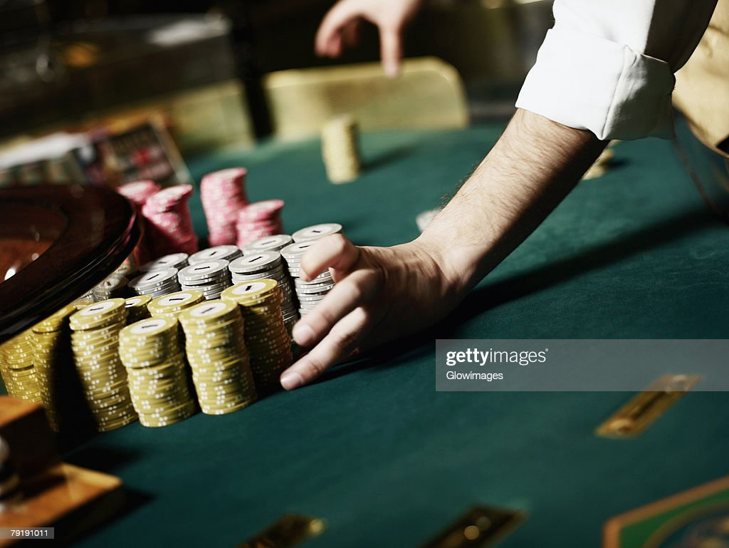Casino worker's hand arranging gambling chips on a gambling table : Foto de stock