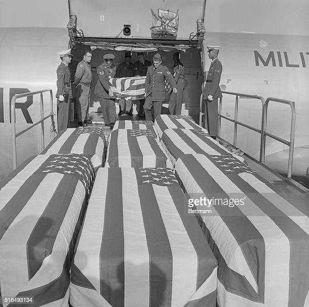 Caskets containing the bodies of nine US servicemen killed in Vietnam are unloaded from USAF transport plane in which they arrived here 2/11 from...