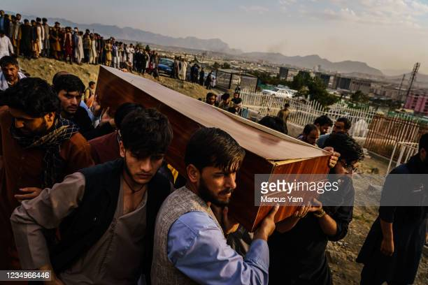 Caskets for the dead are carried towards the gravesite as relatives and friends attend a mass funeral for members of a family that is said to have...