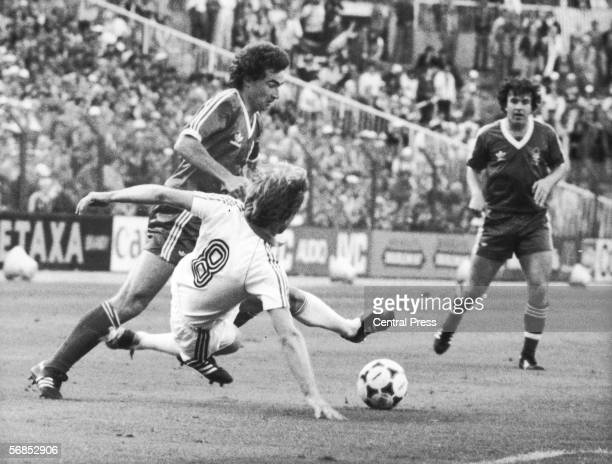 Caspar Memering of Hamburger SV attempts a flying tackle on Martin O'Neill of Nottingham Forest while Garry Birtles looks on during the 1980 European...