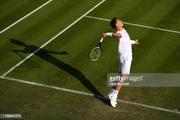Casper Ruud or Norway serves in his Men's Singles first round match against John Isner of The United States during Day two of The Championships -...