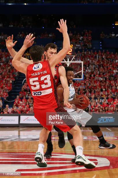 Casper Ware of United drives to the basket against Angus Brandt and Damian Martin of the Wildcats during game three of the NBL Grand Final Series...
