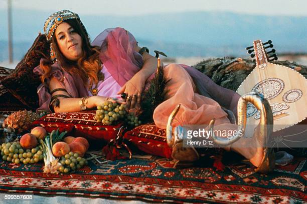 Cass Elliot dressed up in Middle Eastern garb lying on pillows and surrounded by an assortment of fruit