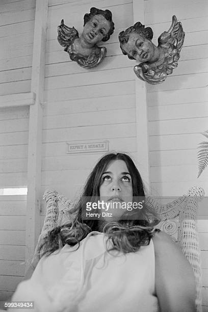 Cass Elliot sits under a pair of angel figurines Posted on the wall above her head is a plaque that reads Expect a Miracle