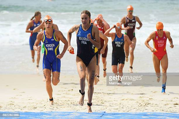Cassandre Beaugrand of France and Lisa Norden of Sweden lead a group out of the water during the Women's Triathlon on Day 15 of the Rio 2016 Olympic...