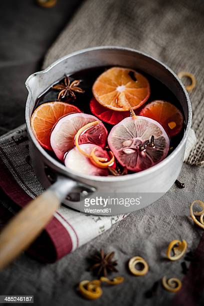 Casserole with mulled wine, slices of lemons and oranges and spices