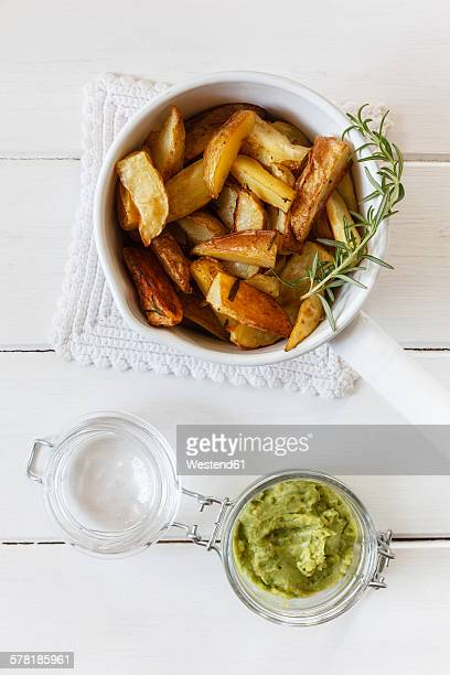 Casserolle of potato wedges with rosemary and glass of pesto