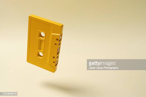 cassette tape floating on yellow background - kunst, kultur und unterhaltung stock-fotos und bilder