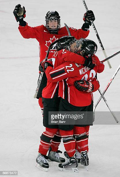 Cassie Campbell and Gina Kingsbury of Canada celebrate with Hayley Wickenheiser after Winckenheiser scored the team's third goal of the game against...