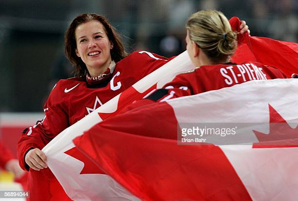 Cassie Campbell and Kim StPierre of Canada hold Canadian flags and celebrate their 41 victory over Sweden to win the gold medal in women's ice hockey...