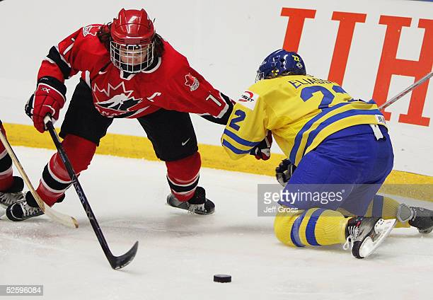 Cassie Campbell of team Canada is pulled down by Emma Eliasson of team Sweden as they fight for the puck in a IIHF World Women's Championships...