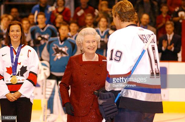 Cassie Campbell watches as Vancouver Canucks captain Markus Naslund hands Queen Elizabeth the hockey puck after the drop at centre ice at General...