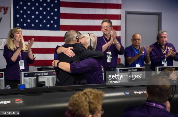 Cassini program manager at JPL Earl Maize left and spacecraft operations team manager for the Cassini mission at Saturn Julie Webster right embrace...