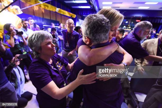 TOPSHOT Cassini science team members Nora Alonge Scott Edgington and Jo Pitesky hug as the final loss of signal from the Cassini spacecraft is...
