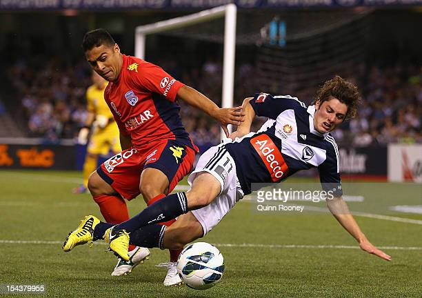 Cassio of United tackles Marco Rojas of the Victory during the round three ALeague match between the Melbourne Victory and Adelaide United at Etihad...