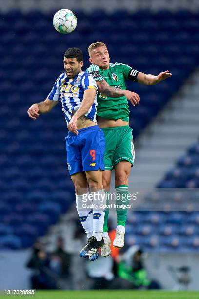 Cassio Scheid of SC Farense competes for the ball with Mehdi Taremi of FC Porto during the Liga NOS match between FC Porto and SC Farense at Estadio...