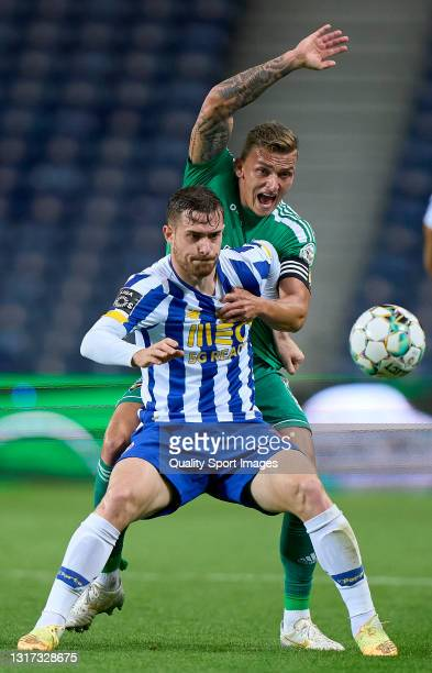 Cassio Scheid of SC Farense competes for the ball with Toni Martinez of FC Porto during the Liga NOS match between FC Porto and SC Farense at Estadio...