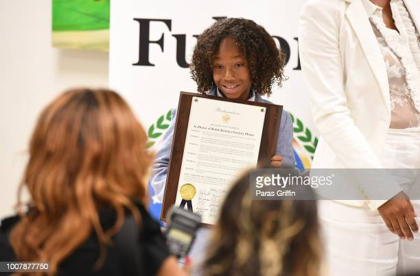 Cassius Brown holds his father proclamation during the Proclamation to Bobby Brown To Honor the Bobbi Kristina Serenity House at South Fulton City...