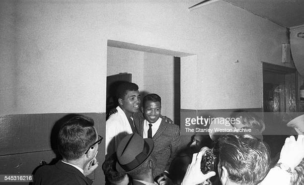 Cassius Clay and former Middleweight champion Sugar Ray Robinson greet the press after his TKO win vs Doug Jones during their heavyweight bout at...