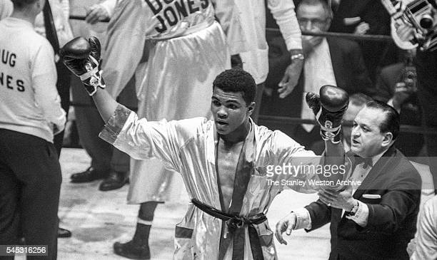 Cassius Clay celebrates his win throwing his arms up in the air after winning the decision vs Doug Jones during their heavyweight bout at Madison...