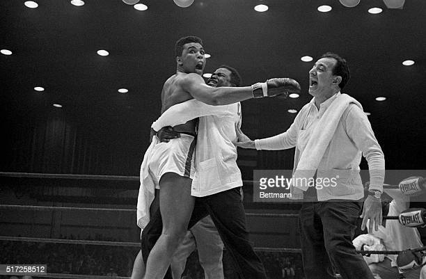 Cassius Clay is embraced by his handlers after he won the world heavyweight championship on a TKO over Sonny Liston in the 7th round.