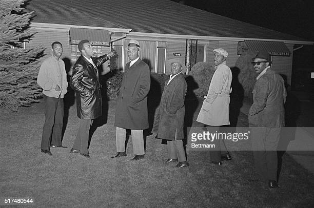 Cassius Clay points to the home of heavyweight champion Sonny Liston and yells, as his companions stare at the reporters gathered here at 1:00 a.m....