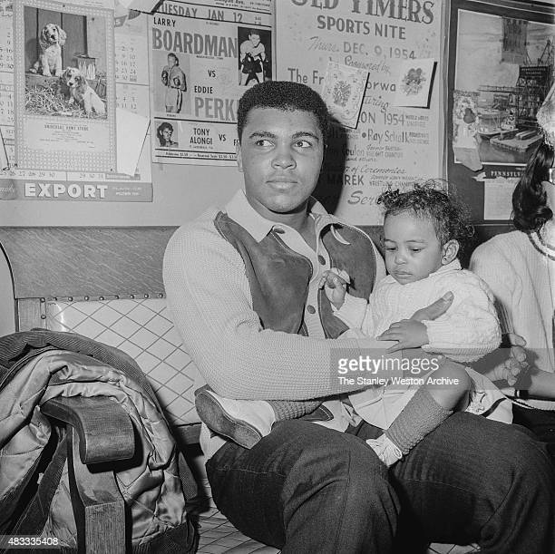 Cassius Clay sits with his daughter after training for his title defense against Sonny Liston on February 22 1965 in Chicago Illinois EDITORIAL ONLY...
