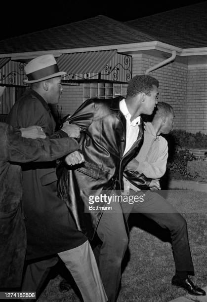 Cassius Clay taunts at the home of heavyweight champion Sonny Liston and yells, as his companions stare at the reporters gathered here at 1:00 a.m....