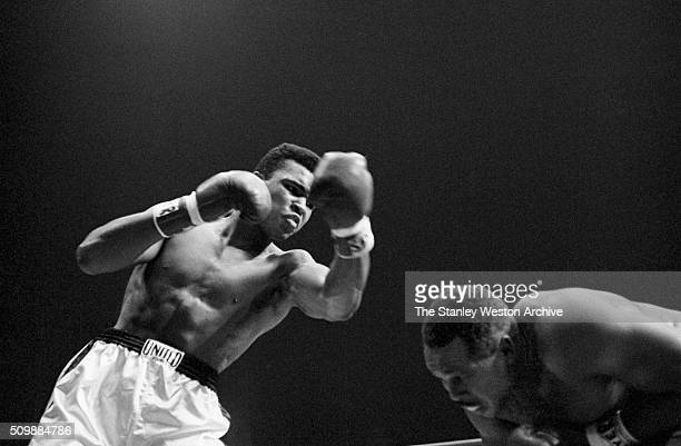Cassius Clay throws a left punch to Archie Moore who ducks below the punch during the fight at the Sports Arena on November 15 1962 in Los Angeles...