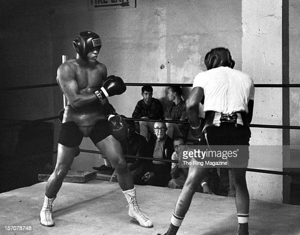 Cassius Clays spars with a partner as he trains for his upcoming fight against Archie Moore in October 1962 in Los AngelesCalifornia