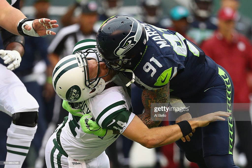 Cassius Marsh #91 of the Seattle Seahawks hits his helmet against quarterback Ryan Fitzpatrick #14 of the New York Jets for a penalty 'Roughing the Passer' in the second quarter at MetLife Stadium on October 2, 2016 in East Rutherford, New Jersey.