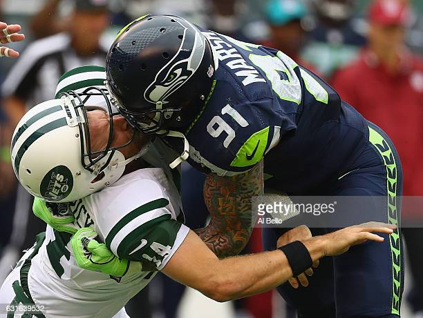 Cassius Marsh of the Seattle Seahawks hits his helmet against quarterback Ryan Fitzpatrick of the New York Jets for a penalty 'Roughing the Passer'...