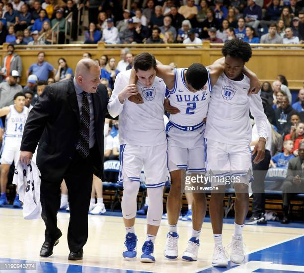 Cassius Stanley of the Duke Blue Devils is helped off the court by teammates after an injury to his leg against the Winthrop Eagles at Cameron Indoor...