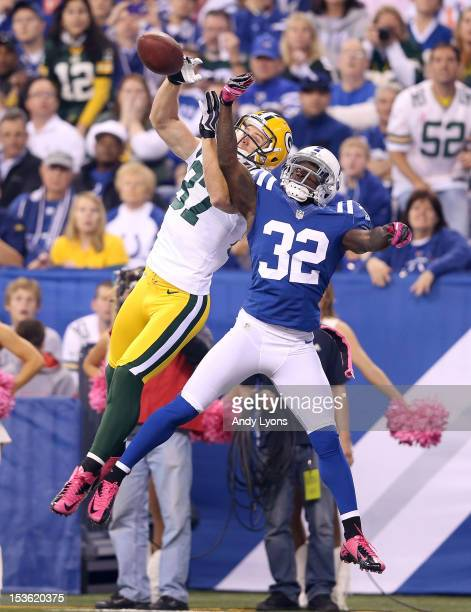 Cassius Vaughn of the Indianapolis Colts and Jordy Nelson of the Green Bay Packers reach for a pass during the NFL game at Lucas Oil Stadium on...