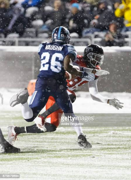 Cassius Vaughn of the Toronto Argonauts picks up the ball after fumble against DaVaris Daniels of the Calgary Stampeders during the second half of...