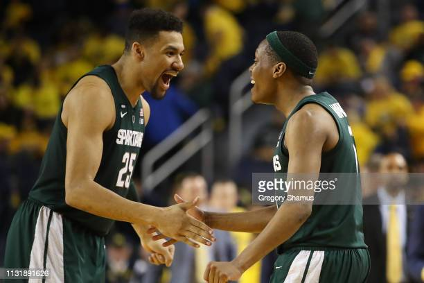 Cassius Winston and Kenny Goins of the Michigan State Spartans react after a 7770 win over the Michigan Wolverines at Crisler Arena on February 24...