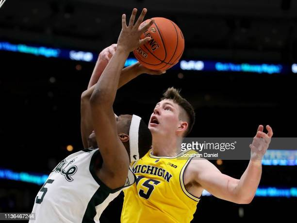 Cassius Winston of the Michigan State Spartans attempts a shot while being guarded by Jon Teske of the Michigan Wolverines in the second half during...