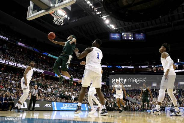 Cassius Winston of the Michigan State Spartans attempts a shot against Zion Williamson of the Duke Blue Devils during the first half in the East...