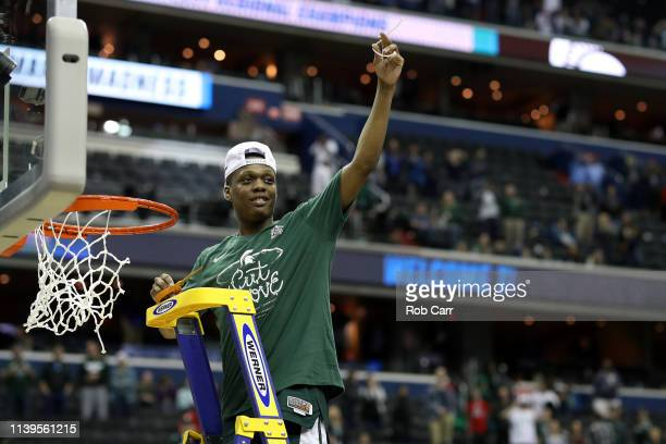 Cassius Winston of the Michigan State Spartans celebrate by cutting down the net after defeating the Duke Blue Devils in the East Regional game of...